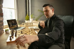 Young Caucasian man chess player playing chess online using laptop.