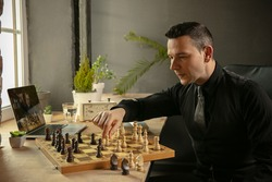 Young Caucasian man chess player playing chess online with his student.