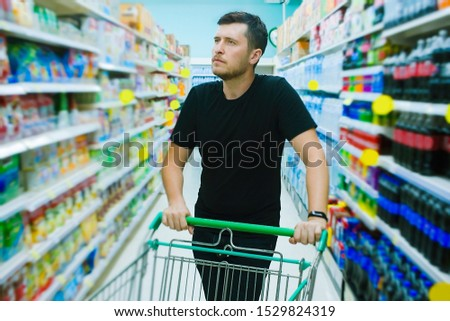 Young caucasian man choosing goods in grocery section of supermarket. Shopping and consumerism concept.