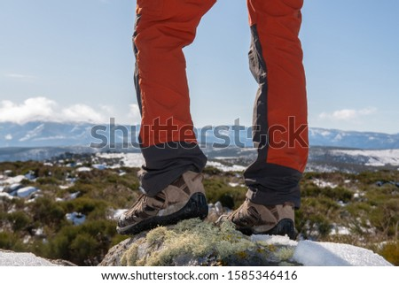 YOUNG CAUCASIAN MAN EQUIPPED WITH MOUNTAIN CLOTHES ENJOYING A TREKING WALK IN SNOWY LANDSCAPE WITH BLUE SKY AND SUNSHINE