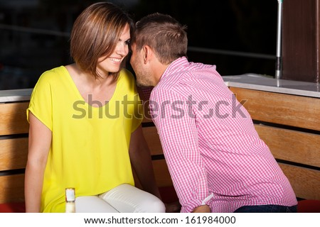 Young Caucasian man flirting with a woman while hanging out at a bar at night