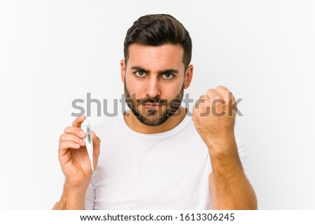 Young caucasian man holding a thermometer isolated Young caucasian man holding  a showing fist to camera, aggressive facial expression.