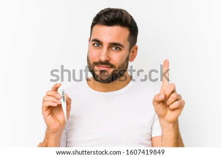 Young caucasian man holding a thermometer isolated Young caucasian man holding  a showing number one with finger.