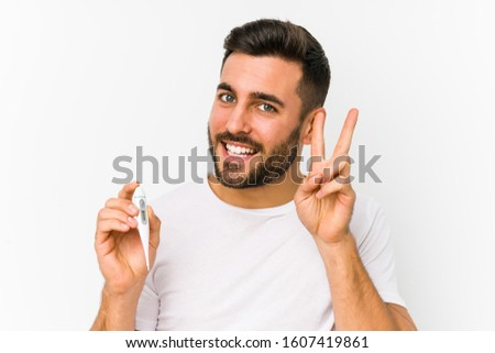 Young caucasian man holding a thermometer isolated Young caucasian man holding  a showing victory sign and smiling broadly.