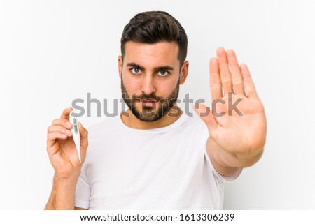 Young caucasian man holding a thermometer isolated Young caucasian man holding  a standing with outstretched hand showing stop sign, preventing you.
