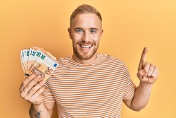 Young caucasian man holding bunch of 50 euro banknotes smiling with an idea or question pointing finger with happy face, number one