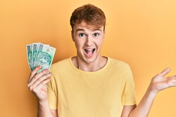 Young caucasian man holding 50 polish zloty banknotes celebrating achievement with happy smile and winner expression with raised hand