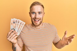 Young caucasian man holding 10 united kingdom pounds banknotes celebrating achievement with happy smile and winner expression with raised hand
