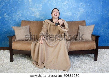 Young Caucasian man in blanket with remote control laughs out loud