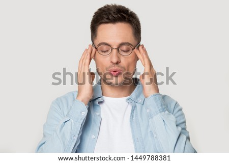 Young caucasian man in eyeglasses massaging temples with close eyes, breathing out, trying to calm down, posing on grey studio background head shot portrait, reducing stress, self-control concept. ストックフォト ©