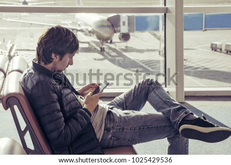 Young caucasian man in jeans and outerwear sitting in chair airport waiting hall and using smartphone. Online remote banking, hotel booking, mobility, reading news, use of 3 G and 4 G network. #1025429536