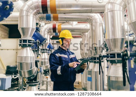 Young Caucasian man in protective suit using tablet while standing in heating plant. Photo stock ©