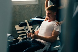 Young Caucasian man in white shirt at a gym, training hard and pulling weights in seated cable row machine. Lifting heavy weights and fatigue. Sport fitness and muscles concept