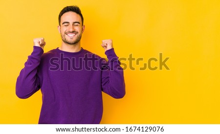 Young caucasian man isolated on yellow bakground celebrating a victory, passion and enthusiasm, happy expression. Сток-фото ©