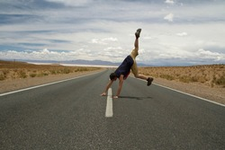 Young caucasian man jumping and twirling in the asphalt road across the arid desert.