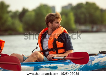 Young caucasian man kayaking on river with sunset in the backgrounds. Having fun in leisure activity. Confident male model placticing on the kayak, smiling. Sport, vacation, holidays concept. Colorful #1525407056