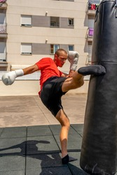 Young caucasian man kicking a punching bag hanging on the street, he trains hard to improve. Contact sport. Training concept