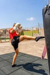 Young caucasian man kicking a punching bag hanging on the street, he trains hard to improve. Contact sport. Training concept.