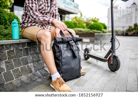 Young caucasian man opens a black roll top backpack while sitting on a bench near an electric scooter in a city park. Courier, delivery service concept. Male with rucksack looks into an open backpack. Сток-фото ©