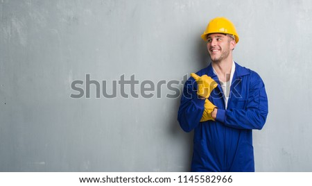 Young caucasian man over grey grunge wall wearing contractor uniform and safety helmet pointing and showing with thumb up to the side with happy face smiling