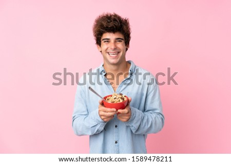Young caucasian man over isolated pink background holding a bowl of cereals