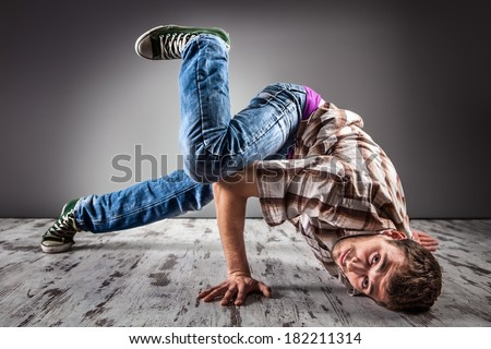 Young caucasian man performing break dance over a gray background/Modern hip-hop style teen breakdancing