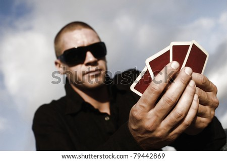 young caucasian man playing cards outside