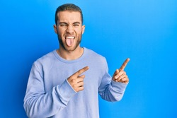 Young caucasian man pointing with fingers to the side sticking tongue out happy with funny expression.