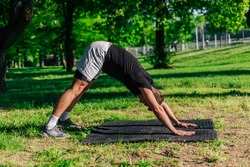 Young caucasian man practicing yoga on a mat outdoors at the park in downward facing dog pose