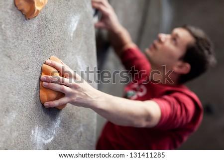 young caucasian man rock climbing indoors - stock photo
