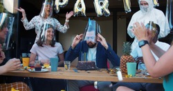 Young Caucasian man shares crazy fun celebration with friends, confetti and masks at COVID-19 birthday party slow motion