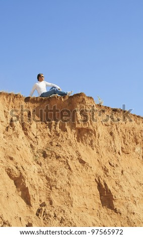 young caucasian man sitting alone over the rock