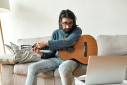 Young caucasian man sitting on sofa at home and adjusting acoustic guitar, watching guitar lesson online on laptop. Music school. Distance education. Focus on man. Stay home, self isolation. Elearning