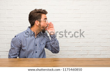 Young caucasian man sitting whispering gossip undertone, trying not to be heard, is warning of a possible weakness or an opportunity
