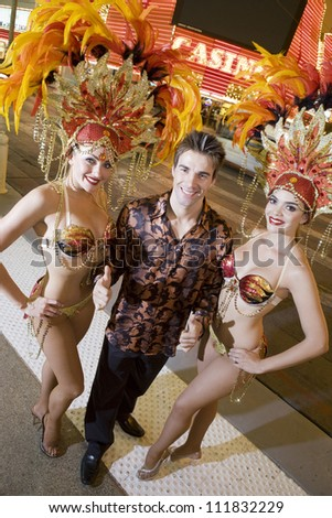 Young caucasian man standing with casino dancers