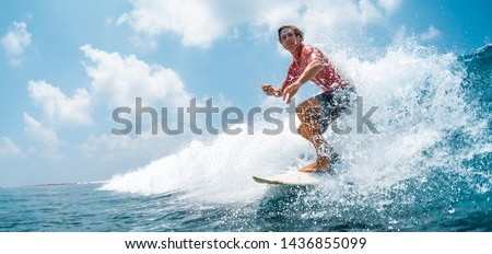 Young caucasian man surfs the ocean wave and makes a lot of splashes into the camera. Chickens surf spot in Maldives #1436855099