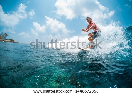 Young caucasian man surfs the ocean wave and makes a lot of splashes into the camera. Chickens surf spot in Maldives #1448672366
