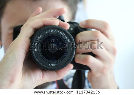Young caucasian man taking selfie picture in a mirror with dslr professional camera