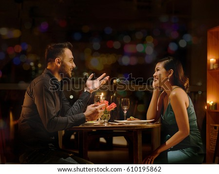 Young Caucasian man telling funny stories to his Vietnamese girlfriend during romantic date #610195862
