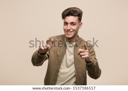Young caucasian man wearing a brown jacket cheerful smiles pointing to front.
