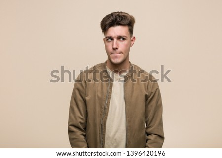 Young caucasian man wearing a brown jacket confused, feels doubtful and unsure.