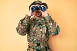 Young caucasian man wearing camouflage army uniform using binoculars puffing cheeks with funny face. mouth inflated with air, catching air.