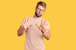 Young caucasian man wearing casual clothes and glasses moving away hands palms showing refusal and denial with afraid and disgusting expression. stop and forbidden.
