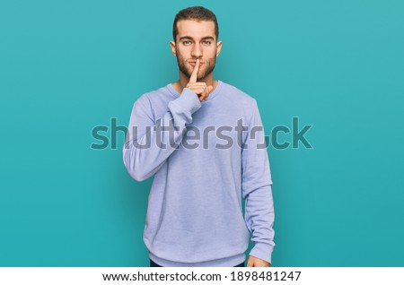 Young caucasian man wearing casual clothes asking to be quiet with finger on lips. silence and secret concept.