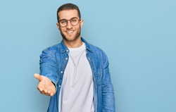 Young caucasian man wearing casual clothes smiling cheerful offering palm hand giving assistance and acceptance.