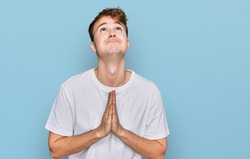 Young caucasian man wearing casual white t shirt begging and praying with hands together with hope expression on face very emotional and worried. begging.
