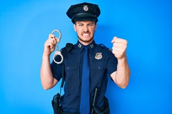Young caucasian man wearing police uniform holding handcuffs annoyed and frustrated shouting with anger, yelling crazy with anger and hand raised