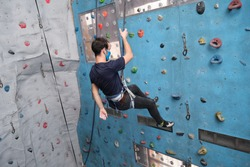 Young caucasian man wearing protective face mask rappelling at indoor artificial rock climbing wall. New normal concept.