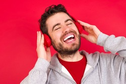 Young caucasian man wearing tracksuit over red background smiles broadly feels very glad listens favourite music track via wireless headphones closes eyes.