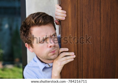 Young caucasian man with agoraphobia spying and looking out the door. He is afraid of communication with people